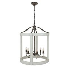 This oversized wooden lantern features a painted drumcage surrounding a wrought iron 6 light center. It features decorative medallions on a simple silhouette t