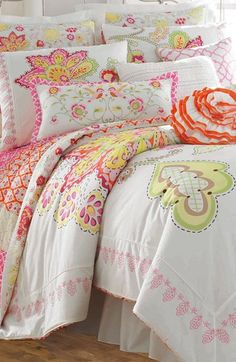 Bright florals by Dena™ Home add energetic style to a vibrant comforter framed by pink leaf embroidery. The comforter reverses to a pink and red design.