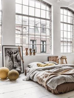 bright sunny big windowed loft // oversized photography // high ceilings // bed on the floor // whitewashed everything