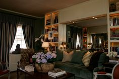 green velvet sofa + dark walls + bookcases + table displays via Stylebeat