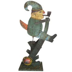 1stdibs.com | Circa 1920 double sided metal balance toy depicting a gnome figure sitting on a base that is cut, formed and painted to resemble a tree top, perfectly balanced to rock back and forth when gently pushed