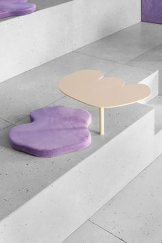 Puddle-shaped cushions in the same fabric perch on stepped concrete seating, between irregular-shaped tables that look like 2D blobs of cream or sprinkles.