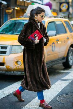 Leandra Medine usa casaco de pele fake alongado , calça jeans, meia aparente vermelha, mocassim e brinco grande.