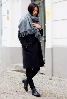 A gray scarf is worn with a black coat, skinny jeans, and ankle boots