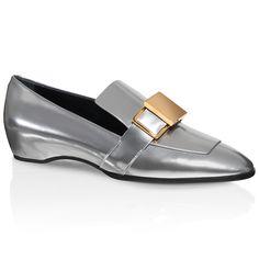 Mokassin aus Leder mit metallischem Effekt. Oversize-Lasche, Maske mit geometrischem Detail aus Metall, schmale Schuhspitze, Ledersohle und kleiner interner Keilabsatz.
