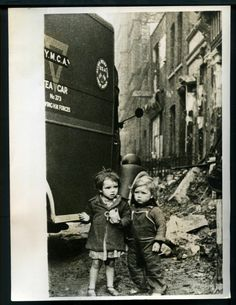 Two children deep in thought as they partake of refreshments beside a Y.M.C.A. tea car following a recent raid in the area.