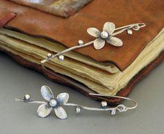 Pendientes de la rama de plata 925 flor con una perla de agua dulce en el centro. Los dos pendientes no son iguales, hay una diferencia entre ellos. Yo les había cepillado para un acabado mate. También disponible con la flor enchapada en oro.  Los pendientes sin los aros tienen 65 mm de longitud.  Usted recibirá en una caja de regalo hermosa por correo certificado.  M A D E a O R D E R: Cada joyería está hecho para pedir que por favor espere de 6 a 10 días antes del envío. Joyería hecha a…