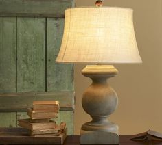BALUSTER TABLE LAMP $279.00 Like a porch baluster found at an architectural salvage, this lamp features cracks and distressing that give it a timeworn patina and hint at many years of use. The base is turned from solid alder wood and finished by hand in a weathered vintage-green. A matching ball finial secures the hardback burlap drum shade.