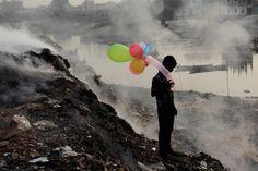 Mención de Honor Personas: Vida a lo largo del río contaminado Un niño juega con los globos por el río Buriganga como el humo emite desde un patio de descarga durante la puesta de sol en Dhaka, Bangladesh. ( Andrew Biraj / National Geographic Photo Contest)