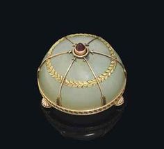 A GEM-SET TWO-COLOUR GOLD-MOUNTED BOWENITE BELL-PUSH  MARKED FABERGÉ, WITH THE WORKMASTER'S MARK OF MICHAEL PERCHIN, ST PETERSBURG, CIRCA 1890  Circular, on three gadrooned ball feet, the body applied with a green gold laurel border and rose gold arrows pointing towards a cabochon garnet push-piece, the lower border chased with Greek fret pattern, with an ivory plate under base