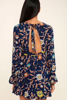 Frolic through the meadows in the Open Country Navy Blue Floral Print Long Sleeve Dress! Gauzy woven fabric in an allover navy blue, orange, yellow, and teal floral print shapes a V-neckline and long sleeves with ruffled, elasticized cuffs. Tying, open back and set-in waist top a flirty skater skirt.