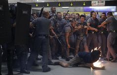 Riot police and security officers clash with a demonstrator inside Faria Lima subway station during a protest against fare hikes for city buses, subway and trains in Sao Paulo, Brazil, January 27, 2015.