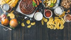#Oktoberfest beer and snacks variety  Beer and snack set. Octoberfest food frame concept. Variety of beers grilled sausages burgers corn fried potatoes chips salted almonds and sauces on dark wooden background. Top view copy space