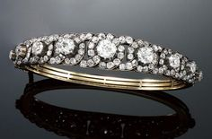 DIAMOND HINGED BANGLE, LATE 19TH CENTURY. Set at the front with a graduated row of nine principal circular-cut diamonds, within surrounds of interlacing design set with cushion-shaped diamonds, length approximately 165mm, fitted case from Henry Lewis, 172 New Bond Street.