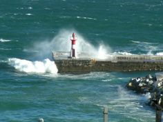 Self catering accommodation, Kalk Bay, Cape Town Close enough to catch a glimpse of a crashing wave over the Kalk Bay lighthouse near the harbour Crashing Waves, Fishing Villages, Cape Town, Bed And Breakfast, Lighthouse, Catering, City, Beach, Travel