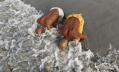 In ginocchio sul Gange. Due fedeli hindu si inginocchiano sulla riva di una spiaggia del Bengala dove confluisce il fiume Gange, a sud di Calcutta, India (Reuters/Rupak De Chowdhuri)