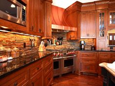 Cherry cabinets, stone back splash, wood floor, black counter