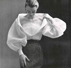 Hubert de Givenchy's white organdy blouse with wide sleeves, deep décoletté is crossed by a modesty fan pleat. Photographed by Phiippe Pottier, 1952.