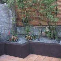 Concrete block planters. Horizontal wood slat screen. Bamboo.