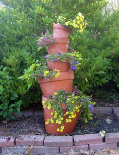 Flowers cascade down this beautiful crooked flower tower of annuals. Searching for something to give the garden a bit of pizazz? Look no further than this crooked terra cotta flower tower. Annual flowers cascade over the sides of each pot like a...