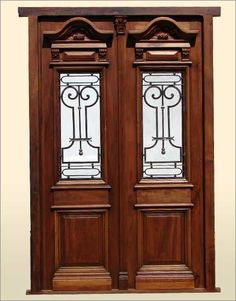 Lovely Double entry door made in solid Mahogany wood and prehung on its frame with amazing hand forged hinge. The hand carved details are very delicate and behind the iron inserts you have hinged glasses to open and close them.
