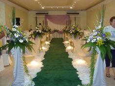 Igreja decorada com tapete verde e arranjo de flores com base em TNT