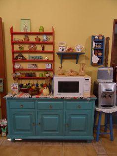 Uma prateleira de uma antiga coleção de latinhas, do filho que cresceu, virou um espaço colorido e aconchegante na cozinha