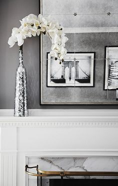 Gray living room detail. Antique finished distressed mirror, white orchids in a mirrored vase on the off-white mental decorated with marble. Retro photos reflected in the mirror.