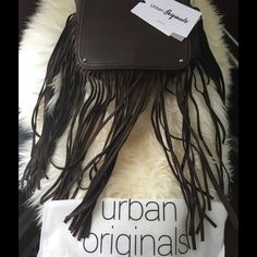 """Urban Originals Free Spirit Crossover NWT Urban originals crossover bag in original dust cover bag. Color brown. Brand new with tags and original packaging from Nordstrom Rack. Adjustable strap. Fold over magnetic snap flap. Fringe detailing. Interior features zip wall pocket and 2 media pockets. Approx 7.5"""" H X 7.5 W X 1.25"""" D. Strap drop 17.5""""-23.5"""". Urban Originals Bags Crossbody Bags"""