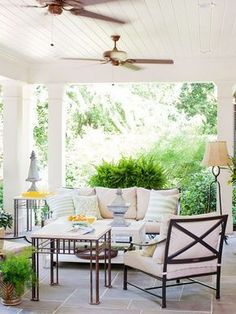 Create a seamless transition to an outdoor sitting area by paying the same attention to detail as you would when decorating indoors. Here, the variation in tile size adds interest and a subtle hint of pattern to this clean porch design, columns add architectural support and a classical vibe, and a beaded-board ceiling adds texture. Two porch ceiling fans circulate air and keep the space cool and refreshing.