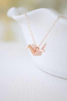 Give this beautiful origami crane as a symbol of everlasting love. This petite rose gold origami charm measures 7/8 inch x 7/8 inch x 3/8 inch and rests on a 18 inch chain. Cranes are symbolic of love