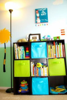 The Dr. Seuss Cat in the Hat painting decorating the wall over our baby's nursery bookshelf. The first thing we did in to decorate our baby's Dr. Seuss Truffula Trees Nursery was paint the room! I knew I wanted the room to look have a look of the