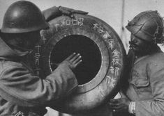 Two Imperial Japanese Army infantrymen inspect an old cannon at a captured fortification in Nanking, possibly at the Zhonghua Gate, 1937.