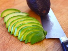 To slice avocados for salads or guacamole, split them in half, remove the pit by whacking it with the heel of your knife and twisting it out, then slice it directly in the skin using the tip of a paring knife or chef's knife. When you then scoop it out with a spoon, you'll have slices ready to go, with less mess than trying to fiddle with slippery peeled avocado a cutting board.