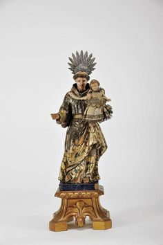 Designação: Santo António com o Menino Jesus; Material: escultura em madeira policromada e dourada; Descrição: base em madeira entalhada e dourada, ...