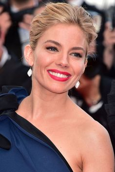 Give traditional red lipstick a fresh update by adding a hint of hot pink to it—only noticeable if you get up close and personal. Sienna Miller shows just how good the shade looks with peach blush.