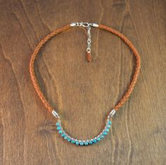 -Turquoise, Sterling Silver, Deer Hide Leather  -Length = 19 Inches + 2 Inch Extender Chain    With this necklace I set out to design a piece of statement jewelry that wasn't fussy, clunky, and was easy to wear.  The focal point of this necklace is a 2 1/2 inch wide by 1 3/8 inch tall silver fill crescent adorned with faceted turquoise beads.  This handmade station hangs from 2, saddle tan deer hide, braided cords that are 1/4 inch in diameter.  The entire piece is finished off with 925…
