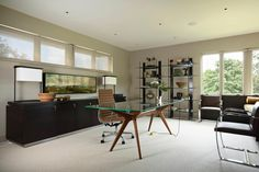 The furniture in this contemporary home office boasts slim silhouettes, clean lines and smooth surfaces for a crisp, sleek look. A midcentury modern desk centers the room, adding a touch of the unexpected.