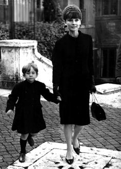 The actress Audrey Hepburn photographed with her son Sean H. Ferrer at Piazza Trinità dei Monti in Rome (Italy), in December 1964.  Audrey was wearing:  • Suit: Givenchy (of black wool, short coat with a small collar in the mandarin style,...