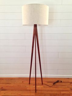 The sleek, tapered legs of this beautiful mahogany tripod floor lamp will blend well with almost any style of home decor. It is constructed with a 3 way, brass plated lamp socket that will accept up to a 150 watt bulb and includes a 10 shade harp. The lamp cord is recessed into one of the legs for a clean, neat look and extends approx. 7 feet.  This lamp is made from solid Sapele Mahogany and finished with a hand rubbed oil and wax technique that highlights the beauty of the wood grain…