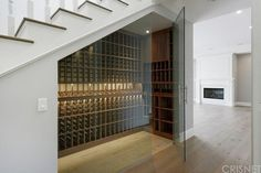 Love this clever wine cellar...it utilizes the often forgotten dead space under the stairs. Genius and super chic with the glass panels and recessed lighting!