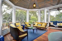 This spectacular porch on a beach house sports the colors of the sky and sun -- the vibrant blue and yellow feel at once nautical and inspiring. Screening in the porch keeps the bugs and other pests at bay. Reclaimed floors and ceilings pay homage to the history of the old seaside town.
