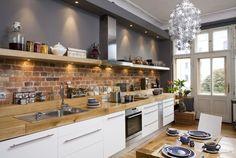 Aranżacja kuchni z cegłą pasuje do nowoczesnych wnętrz. Ściana z  cegły w otoczeniu chromowanych dodatków i nowoczesnych mebli będzie  wyglądała dizajnersko i ciekawie. Zobacz 10 ładnych inspiracji na  aranżację kuchni z cegłą!