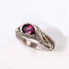 An ancient symbol of paradise in the mid-East, of faithful lovers in China and of protection in Nepal, trees have often served as humanity's way to draw closer to nature. The garnet stone Twisted Branch Ring physically affixes the symbol of the tree to the body. Carrie Bilbo handcrafts the ring out of sterling silver and sets the ring with a pink rhodolite garnet stone. Let the ring sparkle while out for a special night, or wear it as an everyday reminder of nature's beauty.