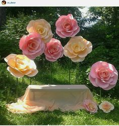giant paper flowers around draped bench .... charming backdrop ...