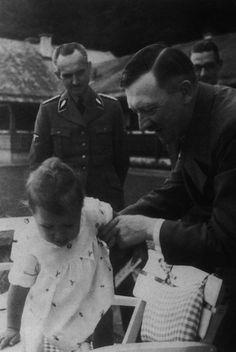 Adolf Hitler helping one of Joseph Goebbels' daughters into her seat at the Berghof in Berchtesgaden, Germany
