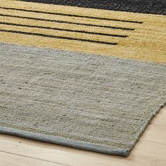 Shop code rug 6'x9'.   Muted flatweave bands together tonal greys, tan and soft blue, accented by clean white triangle and trio of black lines.