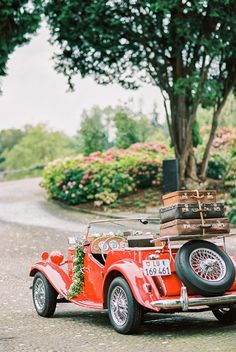 Vintage red getaway car with floral garland | Sandra Marusic Photography | see more on: http://burnettsboards.com/2014/10/glamorous-destination-wedding-switzerland/