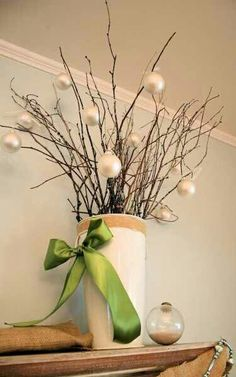 Christmas decor branches with small white ornaments in jar with bow.