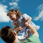 father with her baby playing outdoor against the sky